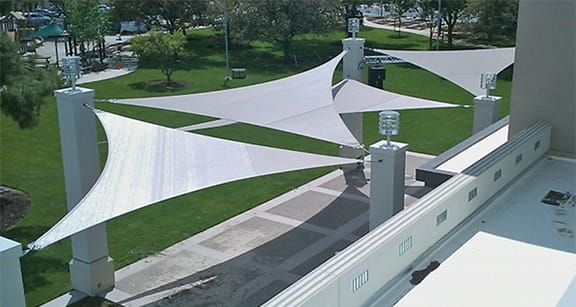 Shade sails covering an outdoor cement patio