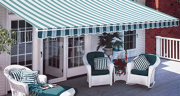 Porch with nice awning overhanging it that matches the green striped chairs under it