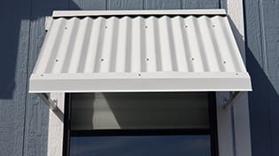 Residential corrugated metal grey window awnings.