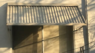 Residential corrugated metal tan window awnings.