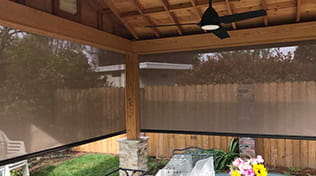 view from inside a patio with outdoor roller shades
